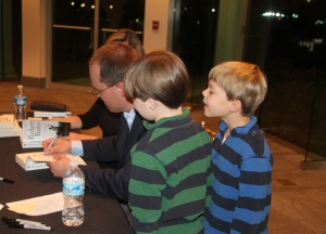 Signing books while my sons Jimmy and Bobby look on.