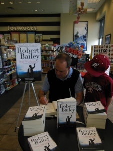 Signing a book while my son Jimmy looks on